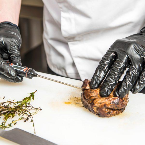 Chef testing meat temperature